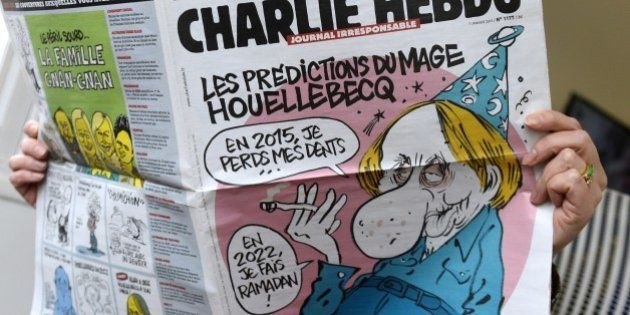 A person reads the latest issue of the French satirical newspaper Charlie Hebdo in Paris on January 7,...