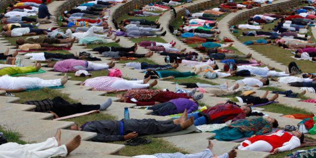 Yoga enthusiasts lie down after performing Surya Namaskar or sun salutation