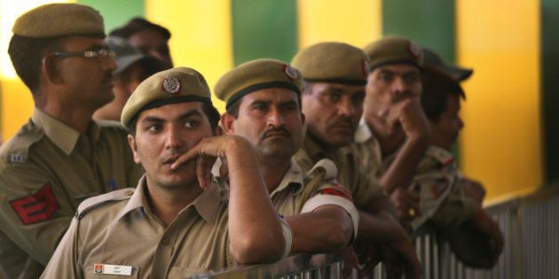 Indian policemen on duty watch election results on television at a counting station in New Delhi, India,...