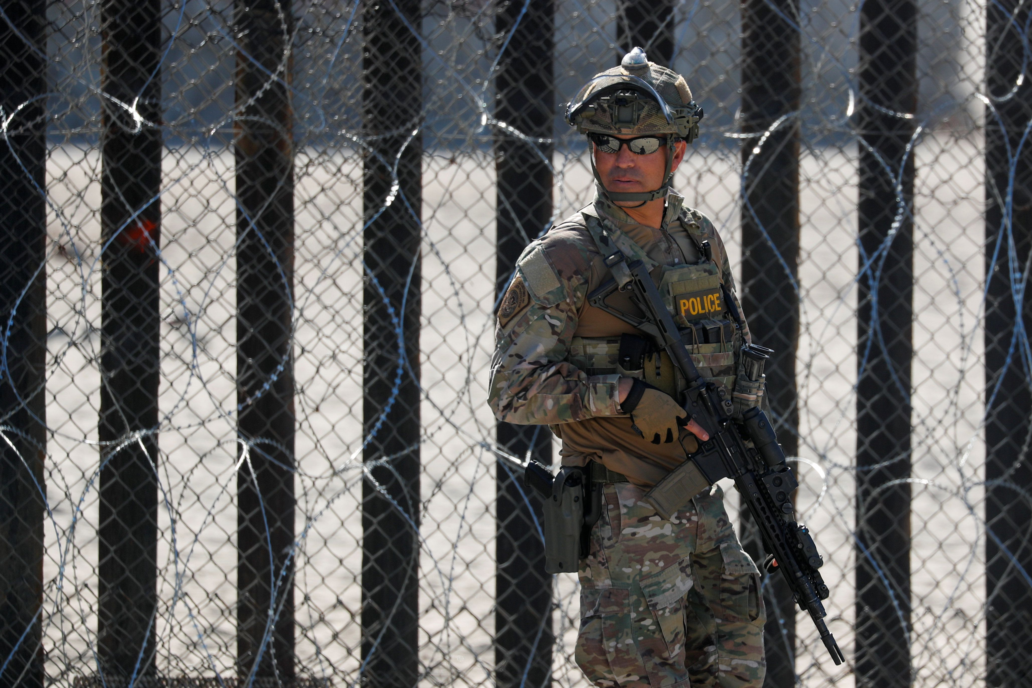 An armed U.S. Customs and Border Patrol agent stands watch at the border fence next to the beach in Tijuana, at the Border State Park in San Diego, California, U.S. November 16, 2018.   REUTERS/Mike Blake
