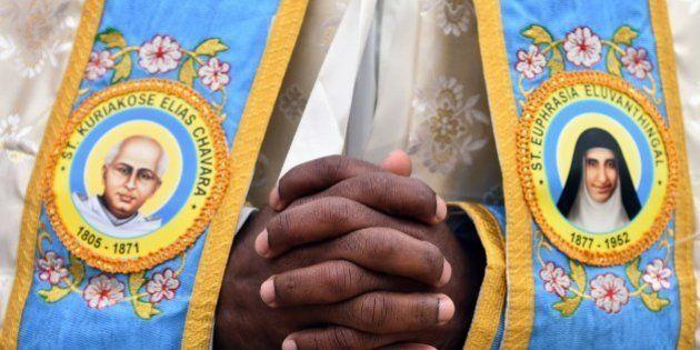 An Indian priest prays prior to a canonization mass for Indian priest Kuriakose Elias Chavara, represented...