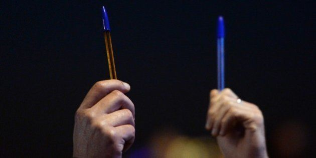 People hold pens in Marseille, southern France, on January 7, 2015, as they take part in a gathering...