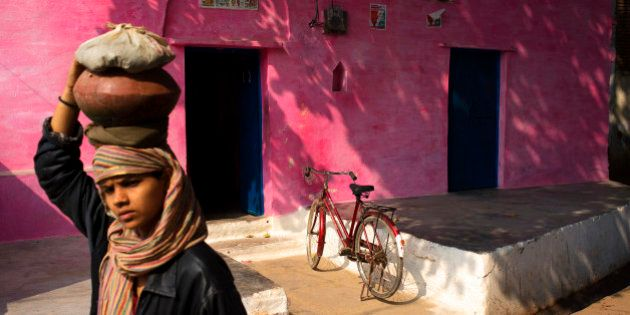 KHAJURAHO, MADHYA PRADESH, INDIA - 2013/12/25: A girl carrying load on her head walks past a house in...