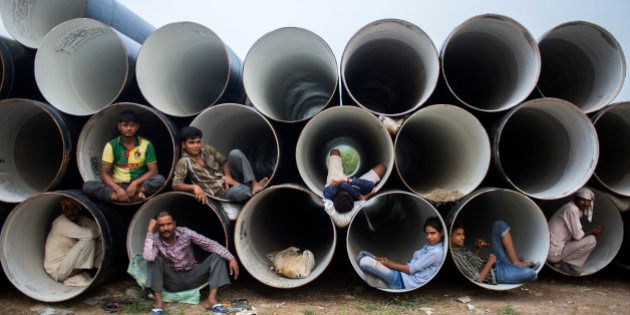 Indian laborers sit inside of pipes after taking shelter from rain in New Delhi on October 13, 2013....