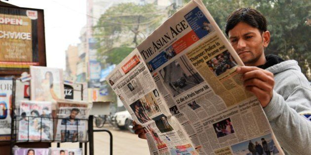 A reader holds up a copy of an English-language Indian newspaper with a front page report on the attack...