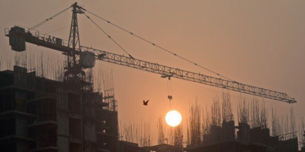Sun rises over an under-construction apartment building on the outskirts of New Delhi early November...