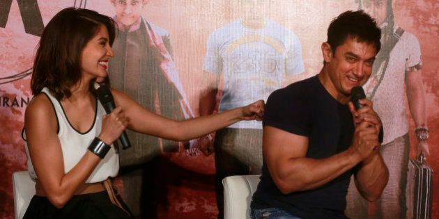 Bollywood actor Anushka Sharma, left, playfully punches co-actor Aamir Khan during the teaser launch...