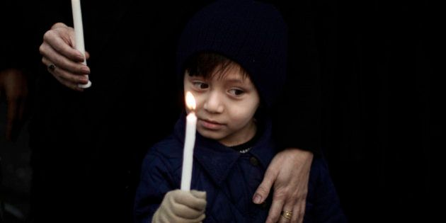 A Pakistani boy holds a candle while he and his mother take part in a protest to condemn Thursday's deadly...
