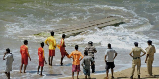 Rescue workers and policemen stand near a boat that capsized, on a beach in Panaji, on the southern coast...