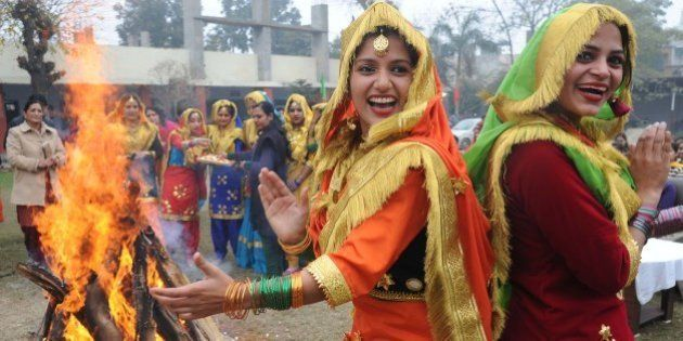 Indian college girls, clad in traditional Punjabi dress, perform the 'giddha' folk dance around a bonfire...