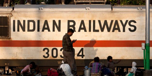 An Indian Railways train engine moves past waiting travellers on a platform at the Hazrat Nizamuddin...