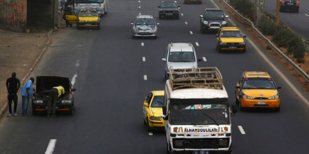 Taxis and other road traffic pass a broken down vehicle on a tarmac road in Dakar, Senegal, on Monday,...