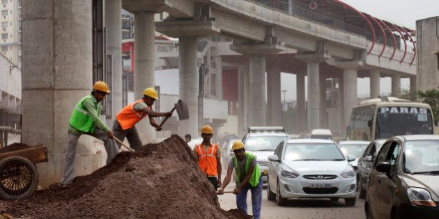 Workers labor at the roadside below an elevated track, operated by Rapid MetroRail Gurgaon Ltd., near...