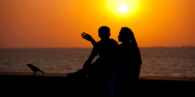 INDIA - MARCH 20: Young Indian couple sit on seawall at sunset at Nariman Point, Mumbai, formerly Bombay,...