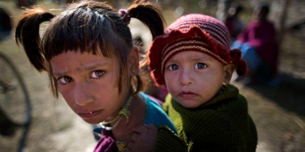 In this Thursday, Dec. 25, 2014 photo, Indian tribal children react to camera at a relief camp at Tinsuti...