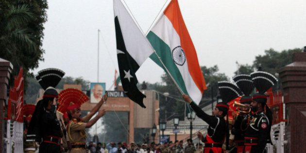 Pakistani border guards perform high kicks during a flag lowering ceremony after a Sunday suicide bombing...