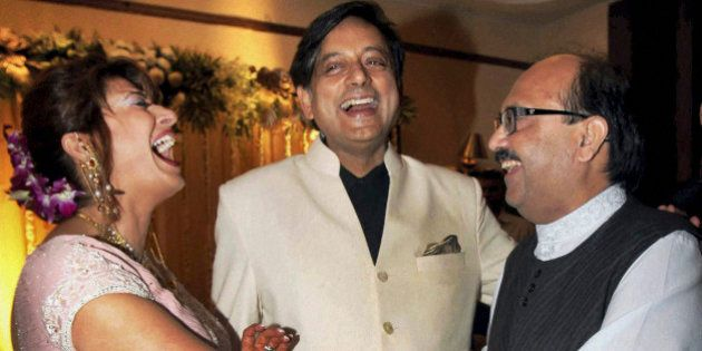 Former Indian Junior Foreign Minister Shashi Tharoor, center, and his wife Sunanda Pushkar are greeted...