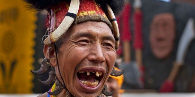 A Naga tribal man in traditional attire laughs as he waits to perform a dance during the Hornbill festival...
