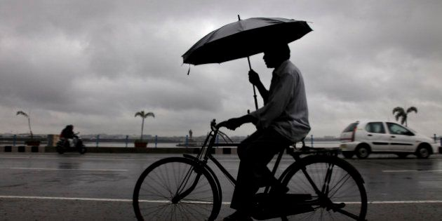 An Indian man keeps himself from rain with an umbrella while riding a bicycle in Hyderabad, India, Friday,...
