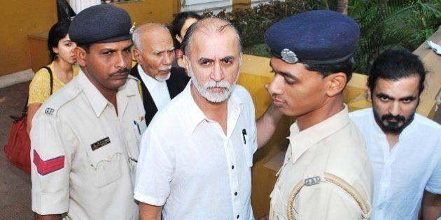 Indian magazine editor Tarun Tejpal (C) is escorted by police officials after a hearing at The High Court...