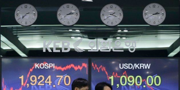 Currency traders pass by screens showing the Korea Composite Stock Price Index (KOSPI) and foreign exchange...