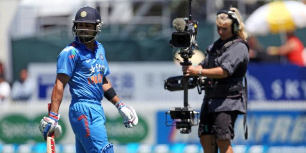 India's Virat Kohli (L) walks off the field after being dismissed during the fourth one-day international...