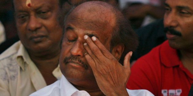 Indian Tamil superstar Rajnikanth gestures as he sits with other Tamil movie stars during a day long...