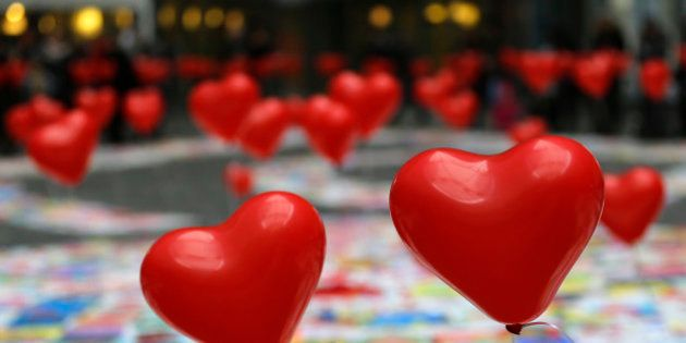 Heart-shaped balloons float as part of an exhibition for children suffering heart diseases in Milan,...