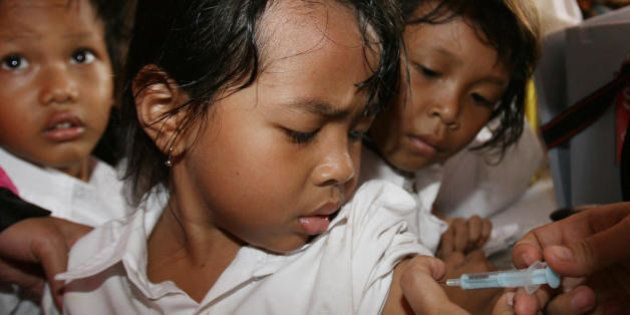 JAKARTA, INDONESIA: Children look as a young girl gets vaccinated in Jakarta, 27 February 2007. IndonesiaIndonesia...