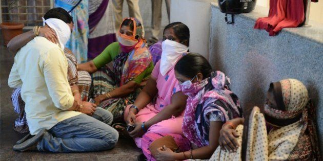 Family members of Indian swine flu patients wait outside the ward at the Gandhi Hospital in Hyderabad...