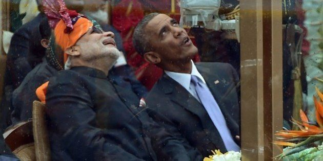 Indian Prime Minister Narendra Modi (L) talks with US President Barack Obama (R) while watching the fly-past...