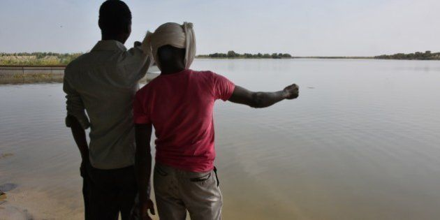 A survivor of a Boko Haram's attack and his friend look at the waters of Lake Chad which borders Chad,...