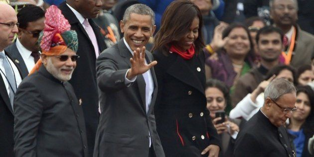 US President Barack Obama (2L) waves to spectators as he leaves with US First Lady Michelle Obama (2R),...