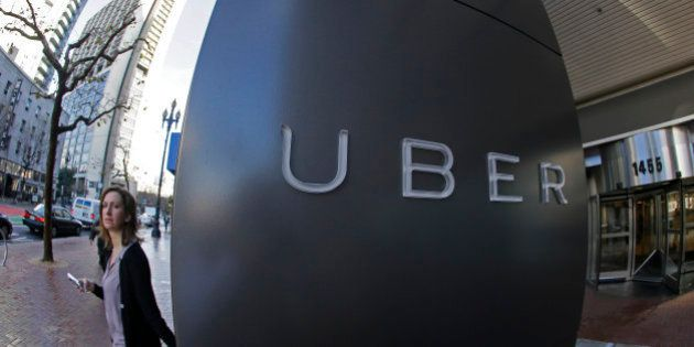 In this Tuesday, Dec. 16, 2014 photo, a woman leaves the headquarters of Uber in San Francisco. Venture capitalists poured a whopping $48.3 billion into U.S. startup companies last year, investing at levels that haven't been seen since before the dot-com bubble burst in 2001, according to a new report issued Friday, Jan. 16, 2015. The two biggest deals in 2014 were separate rounds of investment in Uber Technologies, the high-flying and controversial ride-hailing service, now valued at $41 billion. (AP Photo/Eric Risberg)