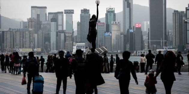 People walk on Victoria harbor waterfront in Hong Kong on January 28, 2015. According to local reports...