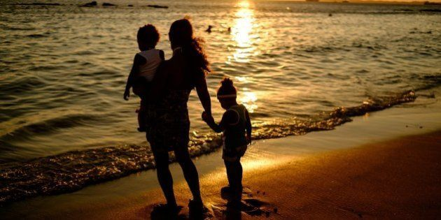 A mother and her children watch the sunset at Boa Viagem beach in Salvador, Brazil, on December 31, 2014....