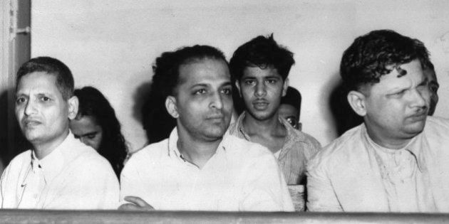 The men accused of the assassination of Mahatma Gandhi listen to testimony in a courtroom during their...
