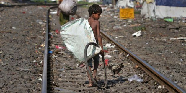 An Indian ragpicker searches for reusable materials from garbage thrown on railway tracks in Gauhati,...