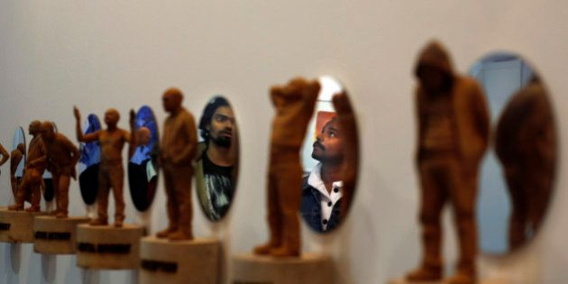 Visitors are reflected on mirrors as they look at an artwork at the sixth India Art Fair in New Delhi,...