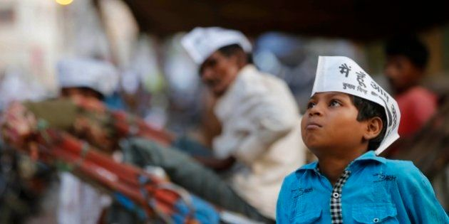 An Indian boy wears an Aam Aadmi Party (AAP), or the common man party, cap during an election rally of...