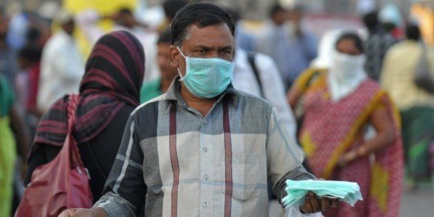 An Indian vendor sells face masks for swine flu prevention outside a railway station in Secunderabad...