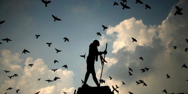 Pigeons fly behind a silhouetted statue of Mahatma Gandhi adorned with garlands on Gandhi's birth anniversary...