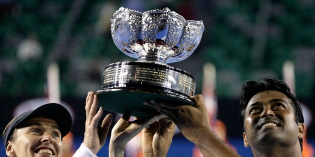 Martina Hingis of Switzerland, left, and Leander Paes of India lift the trophy after defeating Kristina...