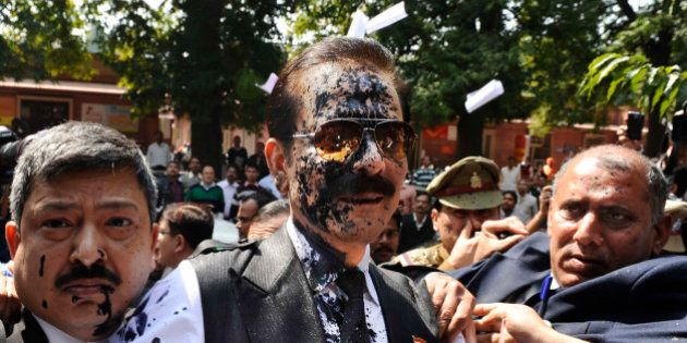 Chairman of Sahara India Pariwar Subrata Roy, his face smeared with ink thrown by a lawyer, walks into...