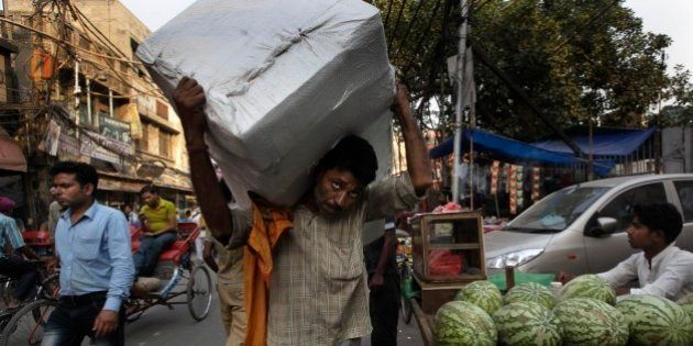 An Indian worker carries hardware components in New Delhi, India, Friday, May 31, 2013. India's economy...