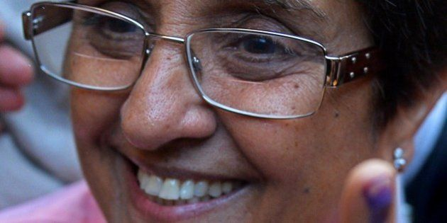 Bharatiya Janata Party (BJP) candidate for Delhi chief minister, Kiran Bedi shows her ink marked finger...