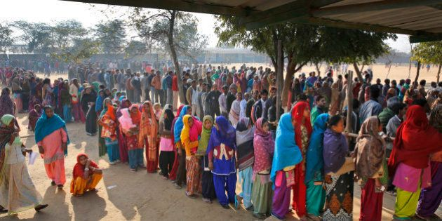 Indians wait in a queue to cast their votes at a polling booth in New Delhi, India, Saturday, Feb. 7,...