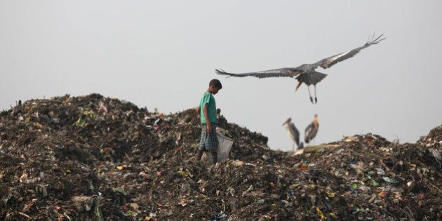 An Indian child looks for recyclable material at a garbage dumping site on the outskirts of Gauhati,...