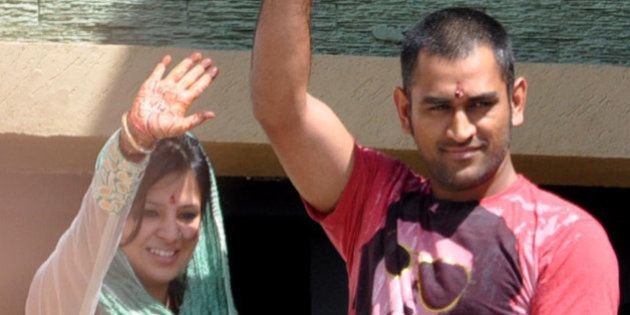 Newly-weds Mahendra Singh Dhoni, Indian cricket team captain, and Sakshi greet fans from the balcony...