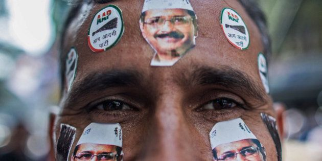 DELHI, INDIA - FEBRUARY 10: A man is seen with Aam Aadmi Party (AAP) leader Arvind Kejriwal stickers...
